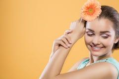 Menina moreno bonita com olhos fechados em um fundo amarelo A mulher guarda a flor do gerbera perto da cabeça Close-up fotos de stock royalty free