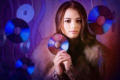 Menina moreno bonita com os CD brilhantes múltiplos Fotografia de Stock Royalty Free