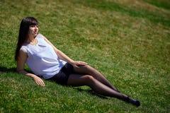 A menina moreno bonita com pés longos na meia-calça preta e na saia curto encontra-se na grama Fotos de Stock