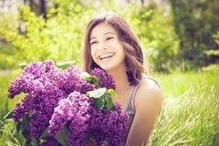 A menina moreno bonita com um lilás floresce o relaxamento e a apreciação da vida na natureza Tiro exterior Copyspace Fotografia de Stock Royalty Free