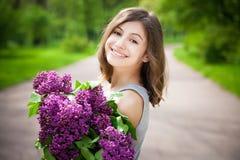 A menina moreno bonita com um lilás floresce o relaxamento e a apreciação da vida na natureza Tiro exterior Copyspace Foto de Stock
