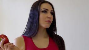 A menina moreno bonita come Apple vermelho em um branco video estoque