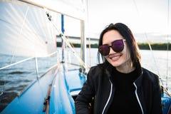 Menina moreno bonita em um revestimento preto em um fundo e em um oceano do c?u Viagem pelo barco ou pelo iate foto de stock royalty free