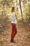 Menina moreno bonita na floresta com uma folha do outono nela Imagens de Stock Royalty Free