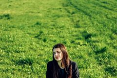 Menina moreno bonita no campo verde ventoso, primavera ensolarada, fotos de stock royalty free