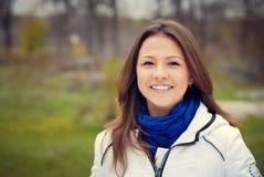 Menina moreno bonita no sorriso branco do revestimento Foto de Stock Royalty Free