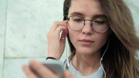 A menina moreno bonita nos vidros em um fundo da parede de mármore cinzenta incluiu a música agradável e aprecia-a video estoque