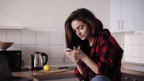Menina moreno bonita nova com cabelo desarrumado na camisa da flanela que senta-se em sua cozinha e que texting alguém filme