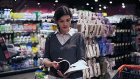Menina moreno bonita nova em seu 20 ` s que folheia através do compartimento no supermercado local filme