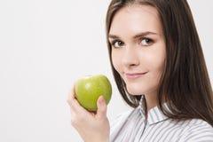 Menina moreno bonita nova em um fundo branco que guarda uma maçã verde fresca fotos de stock royalty free