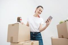 A menina moreno bonita nova em um t-shirt branco embala caixas de cartão com um distribuidor e um esparadrapo escocês esparadrapo imagem de stock