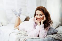 Menina moreno bonita nova que coloca na cama acolhedor com sorriso feliz vestindo da camiseta do inverno de lãs do café, pessoa d Fotos de Stock Royalty Free