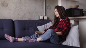 Menina moreno bonita nova que fala a alguém a chamada video da calha ao sentar-se em um sofá video estoque