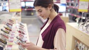 Menina moreno bonita nova que sorri ao escolher um telefone em uma loja da eletrônica Verificando para fora apps no smartphone video estoque