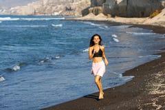 Menina moreno bonita que corre na praia em férias de verão fotos de stock royalty free