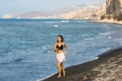 Menina moreno bonita que corre na praia em férias de verão imagens de stock royalty free