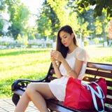 Menina moreno bonita que escreve um parque do telefone da mensagem que senta-se no banco no vestido, mulher de negócio do dia de  Imagem de Stock