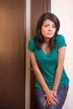 Menina moreno bonita que está na porta do toalete Fotografia de Stock Royalty Free