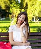 Menina moreno bonita que fala no telefone em um banco de assento do parque no vestido, mulher de negócio do dia de verão que rela Imagem de Stock Royalty Free