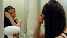 Menina moreno bonita que seca seu cabelo e que olha no espelho em seu banheiro Fotografia de Stock