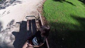 Menina moreno bonita que senta-se apenas no banco na opinião superior do parque filme