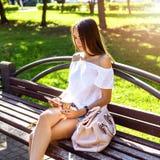 A menina moreno bonita que senta-se em um banco no parque ensolarado do verão, lendo a rede social, aprecia suas férias, estudant Fotos de Stock Royalty Free