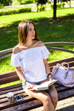 A menina moreno bonita que senta-se em um banco no parque ensolarado do verão, livro de leitura, aprecia suas férias, conceito do Imagens de Stock Royalty Free