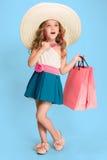 A menina moreno caucasiano pequena bonito no vestido que guarda sacos de compras foto de stock royalty free