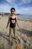 Menina moreno coberta na areia na praia Fotos de Stock