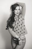 Menina moreno com as calças de brim vestindo do cabelo longo Foto de Stock