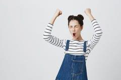 A menina moreno com hairbuns em entusiasmado superior listrado e contente de conseguir a vitória, aperta os punhos, gritos no exc fotos de stock