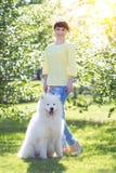 A menina moreno com um cão branco grande fotografia de stock