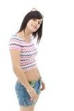 Menina moreno consideravelmente nova com as calças de brim do short no branco Fotos de Stock