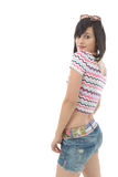 Menina moreno consideravelmente nova com as calças de brim do short no branco Fotografia de Stock Royalty Free