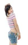 Menina moreno consideravelmente nova com as calças de brim do short no branco Fotografia de Stock