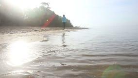 a menina moreno corre ao longo da água no luminoso do nascer do sol