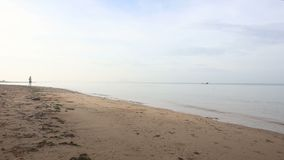 a menina moreno corre perto na praia contra o barco no alvorecer