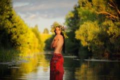 A menina moreno de cabelos compridos em topless na saia vermelha e a grama envolvem-se Imagens de Stock