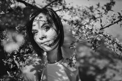 A menina moreno de sorriso bonita com cabelo curto está em um jardim florido da mola com uma árvore de cereja As árvores são cobe foto de stock royalty free