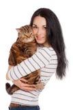 Menina moreno de sorriso bonita e seu gato do gengibre sobre os vagabundos brancos Fotografia de Stock Royalty Free