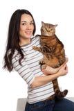 Menina moreno de sorriso bonita e seu gato do gengibre sobre os vagabundos brancos Foto de Stock Royalty Free