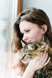 Menina moreno de sorriso e seu gato sobre Fotos de Stock
