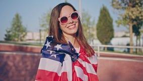 Menina moreno de sorriso feliz bonita do moderno nos óculos de sol no parque do patim envolvido na bandeira americana cheerful video estoque