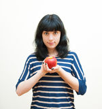 A menina moreno de sorriso mostra a maçã vermelha em suas mãos Imagem de Stock Royalty Free