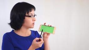 A menina moreno demonstra a tela verde do smartphone em um fundo branco O homem de negócios da menina diz video estoque