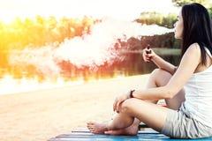 Menina moreno do cabelo longo que fuma o cigarro eletrônico no beac Fotografia de Stock Royalty Free