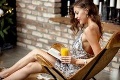 A menina moreno em um vestido de nivelamento cinzento de brilho que guarda um vidro do suco está sentando-se em uma poltrona do d fotos de stock royalty free