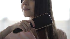 A menina moreno em uma camisa cor-de-rosa está penteando seu pente longo bonito do cabelo vídeos de arquivo