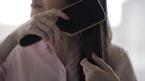 A menina moreno em uma camisa cor-de-rosa está penteando seu pente longo bonito do cabelo video estoque