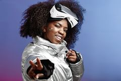 Menina moreno encaracolado moderna vestida em um revestimento prata-colorido que veste em sua cabeça que os vidros da realidade v fotos de stock